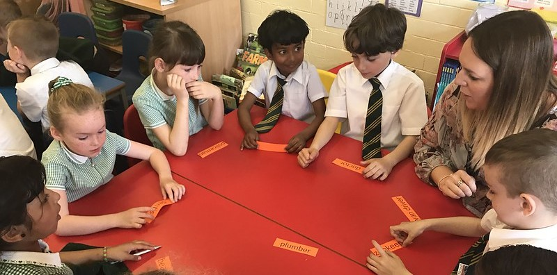 A group of primary children sit around a red classroom table with a volunteer. They each hold a piece of paper which says a different job role.